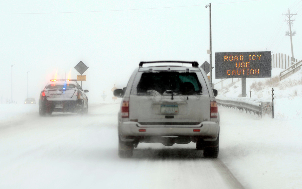 . GOLDEN, CO-April 23, 2013: A police officer hurries past traffic on Highway 93 in Golden heading to and accident, April 23, 2013. Snow and ice made for a slow morning drive in the area. (Photo By RJ Sangosti/The Denver Post)