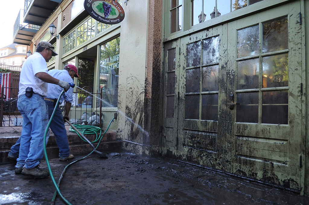 . Flooding that severely damaged numerous homes and businesses along Canon Ave., was in the cleanup stage Tuesday morning. Sudden rains Monday hit the scars from the Waldo Canyon fire of a year ago, causing the flood of mud and debris through the tourist town west of Colorado Springs. (Photo By Steve Nehf / The Denver Post)