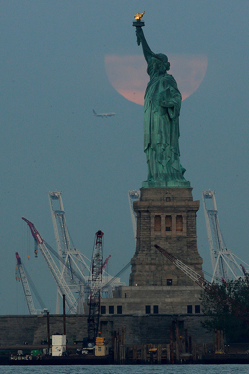 ". With a plane approaching Newark Airport, a ""super moon\"" sets behind a cloud and the Statue of Liberty on Sunday, June 23, 2013, in New York. The larger than normal moon called a \""super moon\"" happens only once this year as the moon on its elliptical orbit is at its closest point to earth and is 13.5 percent larger than usual.  (AP Photo/Julio Cortez)"