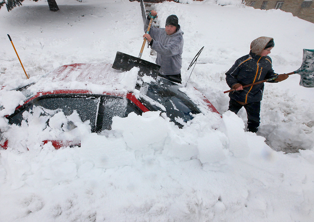 . Luke McHenry, left, his son, Sebastian Wells, dig out their snow-buried vehicle as residents in Madison, Wis. contend with a severe winter storm that moved through the upper Midwest Thursday, December 20, 2012. (AP Photo/Wisconsin State Journal, John Hart)