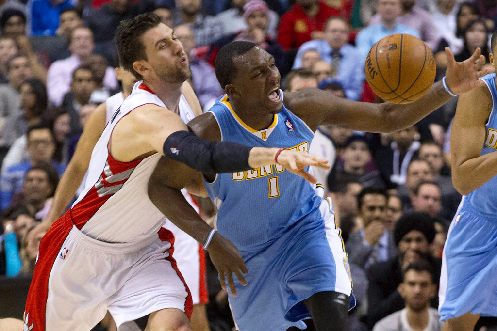 . Toronto Raptors\' Andrea Bargnani, left, vies for a loose ball with Denver Nuggets\' Jordan Hamilton during the second half of an NBA basketball game in Toronto on Tuesday, Feb. 12, 2013. (AP Photo/The Canadian Press, Chris Young)