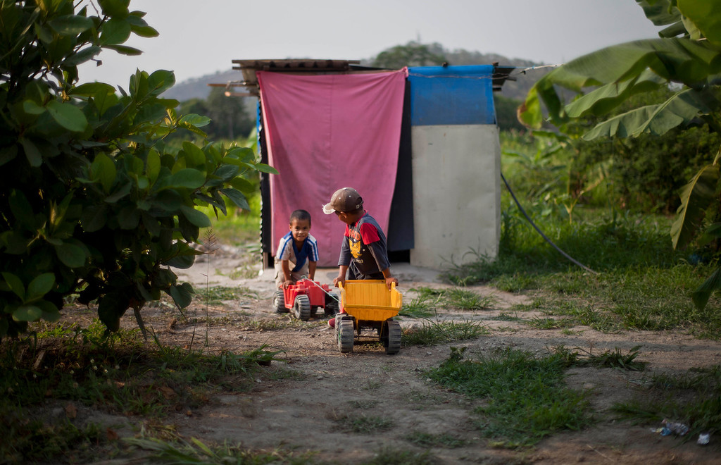 """. In this April 8, 2013 photo, two boys push their toy construction vehicles along a dirt path at a squatter settlement near Tacarigua, Venezuela. Outside Venezuela\'s capital, power outages, food shortages and unfinished projects abound; important factors heading into Sunday\'s election to replace Venezuela\'s late President Hugo Chavez, who died last month after a long battle with cancer. An estimated 2 million of the country\'s nearly 30 million people lack permanent homes, and one of Chavez\'s anti-poverty \""""missions\"""" builds them. But it\'s been slow going. The government says it has built 370,500 homes and apartments over the past two years, and more than 3 million people applied for them. (AP Photo/Ramon Espinosa)"""
