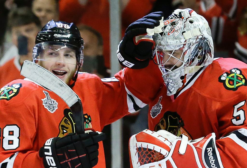 . Chicago Blackhawks right wing Patrick Kane (88) celebrates with goalie Corey Crawford (50) after the Blackhawks beat the Boston Bruins 3-1 in Game 5 of the NHL hockey Stanley Cup Finals, Saturday, June 22, 2013, in Chicago. (AP Photo/Nam Y. Huh)