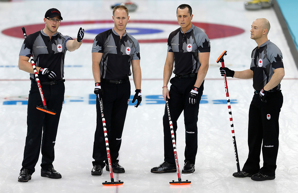. Canada\'s men\'s curling team from left to right, Ryan Harnden, Brad Jacobs, E.J. Harnden and Ryan Fry, discuss their next move during the men\'s curling competition against Denmark at the 2014 Winter Olympics, Thursday, Feb. 13, 2014, in Sochi, Russia. (AP Photo/Wong Maye-E)