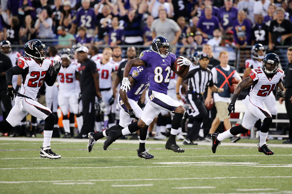 . BALTIMORE, MD - AUGUST 15: Wide receiver Torrey Smith #82 of the Baltimore Ravens outruns  Asante Samuel #22 and Desmond Trufant #21 of the Atlanta Falcons for a touchdown after catching a pass during the first half of a preseason game at M&T Bank Stadium on August 15, 2013 in Baltimore, Maryland.  (Photo by Rob Carr/Getty Images)