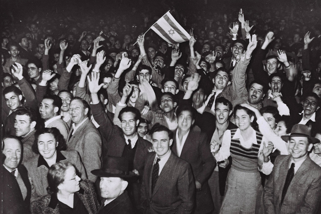 . TEL AVIV, PALESTINE - NOVEMBER 29, 1947: Jubilant residents celebrate with what would become the Israeli flag after the United Nations decision to approve the partition of Palestine November 29, 1947 as crowds gather in front of the Mugrabi cinema in Tel Aviv in the British Mandate for Palestine. (Photo by Hans Pins/GPO via Getty Images)
