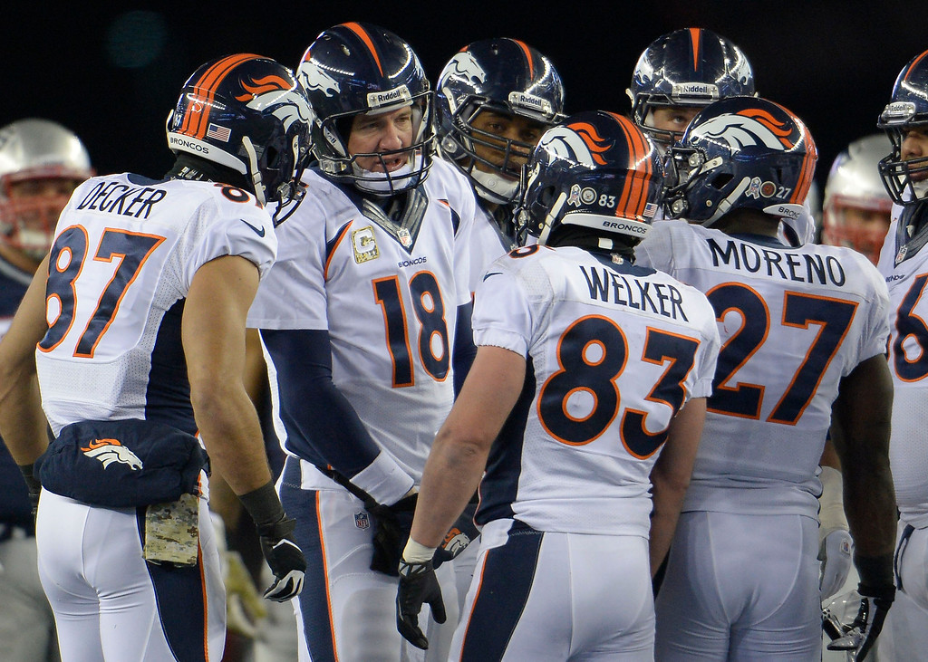 . Broncos quarterback Peyton Manning (18) talks with wide receiver Wes Welker (83) in the huddle during a timeout in the first quarter against the New England Patriots November 24, 2013 at Gillette Stadium. (Photo by Joe Amon/The Denver Post)