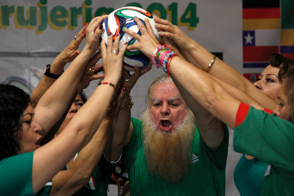 """. Mexico City\'s \""""Great Warlock\"""" Antonio Vazquez, center, and assistants perform a magic ritual using a soccer ball to help Mexico\'s national soccer team reach the quarter-finals of the Brazil World Cup, in Mexico City, Saturday, June 21, 2014. (AP Photo/Moises Castillo)"""