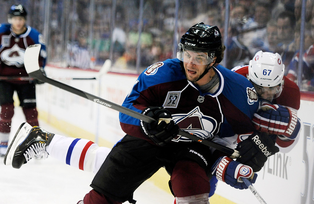 . Colorado Avalanche defenseman Nate Guenin, left, and Montreal Canadiens left wing Max Pacioretty, right, fight for the puck in the second period of an NHL hockey game on Saturday, Nov. 2, 2013, in Denver. (AP Photo/Chris Schneider)