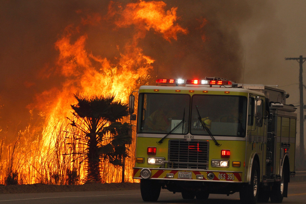 . A fire engine drive past flames from the Springs Fire at Point Mugu State Park May 3, 2013.  REUTERS/Jonathan Alcorn