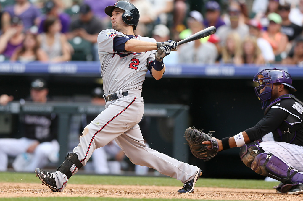 . Minnesota Twins\' Brian Dozier, left, follows the flight of his three-run home run as Colorado Rockies catcher Wilin Rosario looks on in the ninth inning of the Twins\' 13-5 victory in an interleague baseball game in Denver on Sunday, July 13, 2014. Dozier hit a solo home run to lead off the eighth inning as well. (AP Photo/David Zalubowski)
