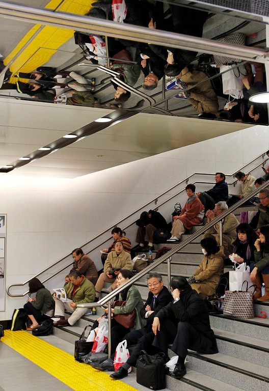 . Commuters sit stranded at Tokyo railway station as train services are suspended due to a powerful earthquake Friday, March 11, 2011. The largest earthquake in Japan\'s recorded history slammed the eastern coasts Friday. (AP Photo/Hiro Komae)