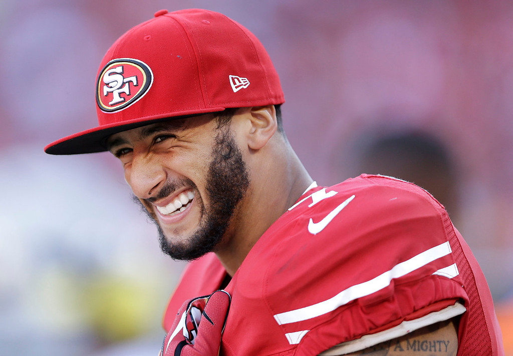 . San Francisco 49ers quarterback Colin Kaepernick smiles on the sideline during the fourth quarter of an NFL football game against the Arizona Cardinals in San Francisco, Sunday, Oct. 13, 2013. The 49ers won 32-20. (AP Photo/Marcio Jose Sanchez)