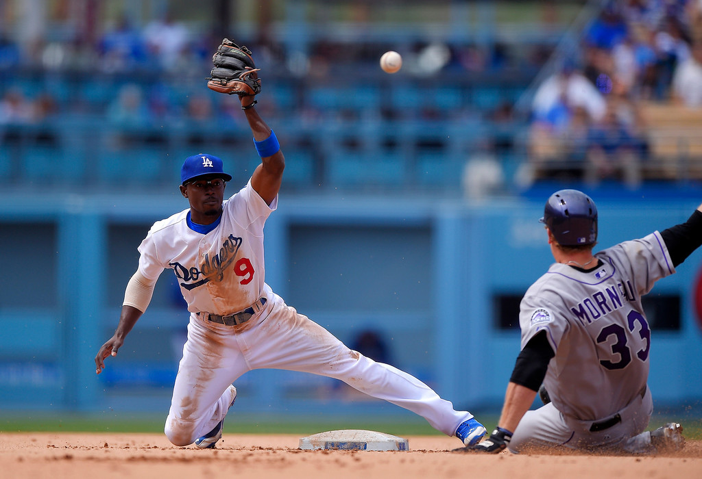 . Colorado Rockies\' Justin Morneau, right, is slides in for a double as the throw from left field goes past Los Angeles Dodgers second baseman Dee Gordon during the sixth inning of a baseball game, Sunday, April 27, 2014, in Los Angeles. (AP Photo/Mark J. Terrill)