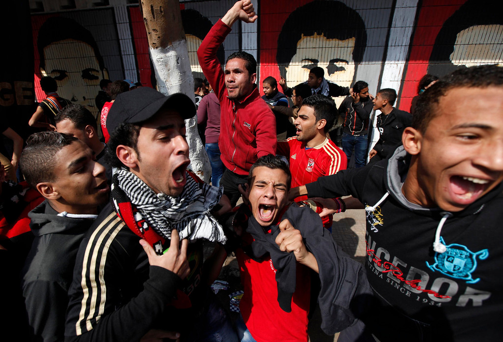 ". Al-Ahly fans, also known as ""Ultras\"", celebrate and shout slogans in front of Al-Ahly club after hearing the final verdict of the 2012 Port Said massacre in Cairo March 9, 2013.  REUTERS/Amr Abdallah Dalsh"