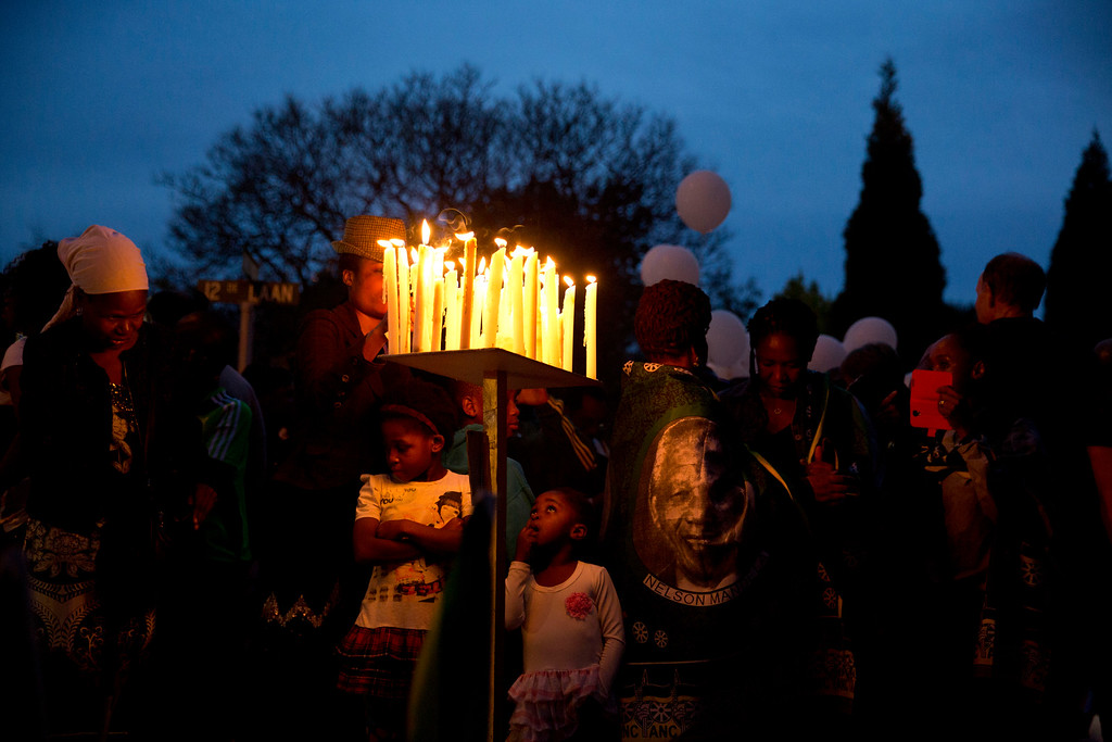 . People stand beside candles burning beside tributes outside the home of former president Nelson Mandela in Johannesburg, South Africa, Saturday, Dec. 7, 2013.   (AP Photo/Matt Dunham)