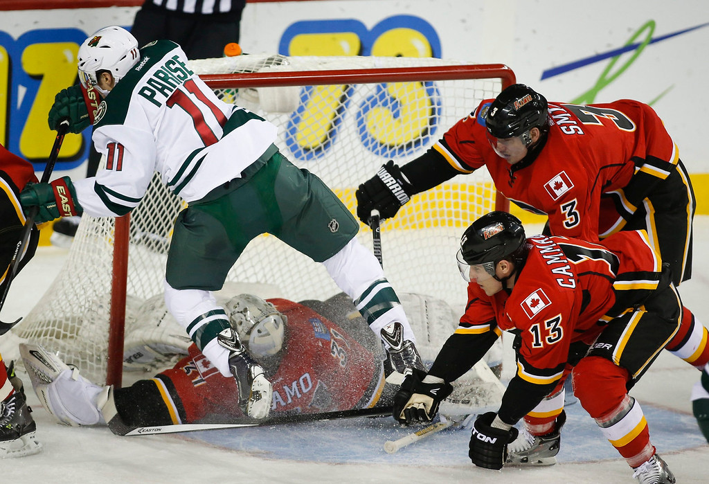 . Minnesota Wild Zach Parise, center, gets slammed into the net by Calgary Flames\' Ladislav Smid, right, from the Czech Republic, during the first period of an NHL hockey game, Saturday, Feb. 1, 2014 in Calgary, Alberta. (AP Photo/The Canadian Press, Jeff McIntosh)