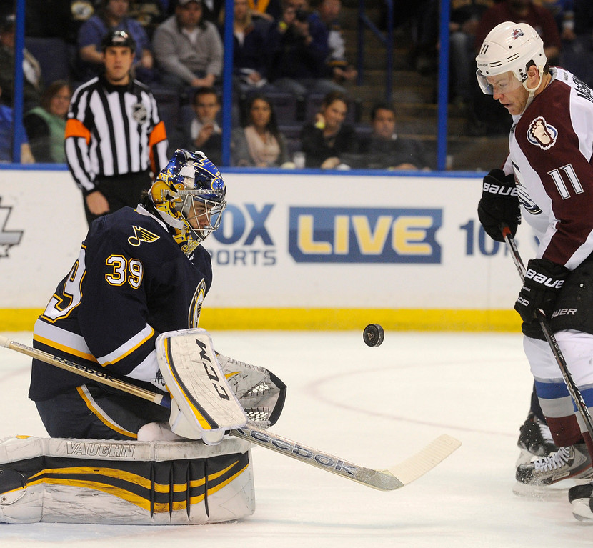 . St. Louis Blues\' goalie Ryan Miller (39) blocks a shot by Colorado Avalanche\'s Jamie McGinn (11) during the first period of an NHL hockey game, Saturday, April 5, 2014, in St. Louis. (AP Photo/Bill Boyce)