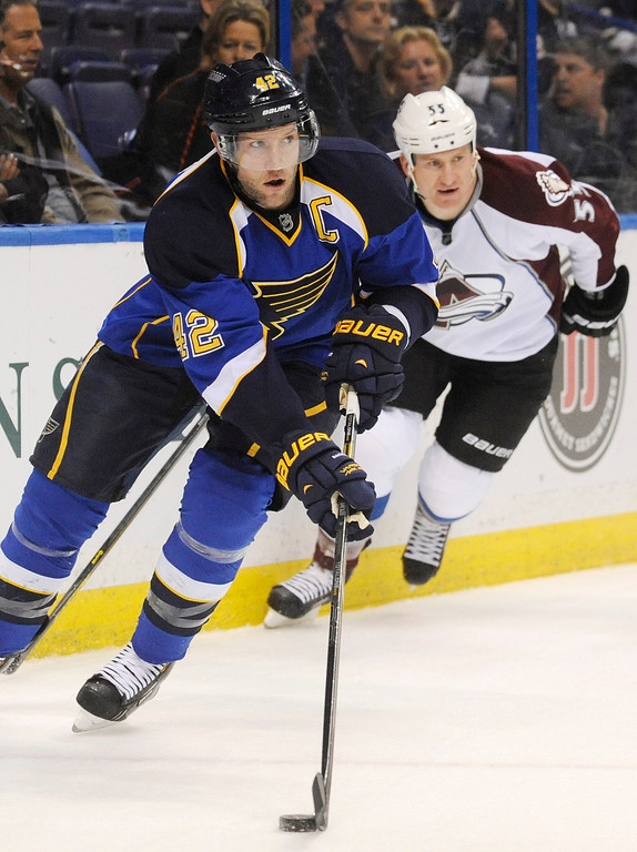 . St. Louis Blues\' David Backes (42) skates around Colorado Avalanche\'s Cody Mcleod (55) in the first period of an NHL hockey game Tuesday, April 23, 2013, in St. Louis. (AP Photo/Bill Boyce)