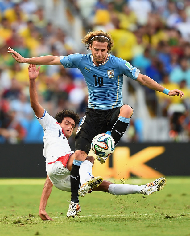 . Yeltsin Tejeda of Costa Rica tackles Diego Forlan of Uruguay during the 2014 FIFA World Cup Brazil Group D match between Uruguay and Costa Rica at Castelao on June 14, 2014 in Fortaleza, Brazil.  (Photo by Laurence Griffiths/Getty Images)