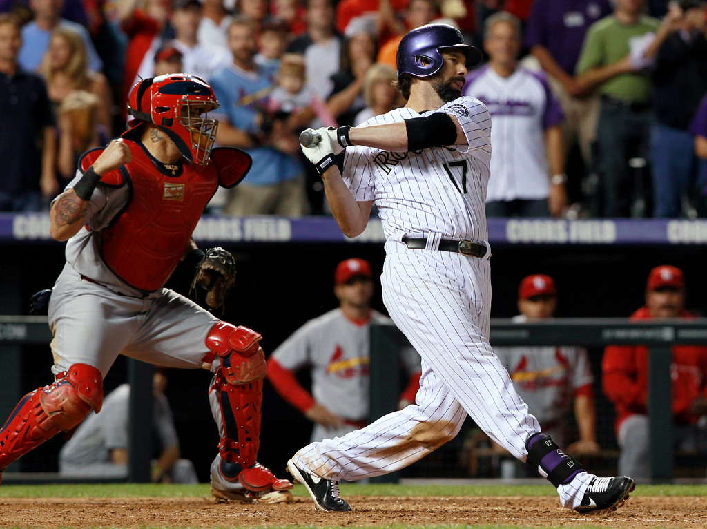 . St. Louis Cardinals catcher Yadier Molina, left, starts to celebrate after Colorado Rockies\' Todd Helton struck out with the bases loaded for the final out in the Cardinals\' 4-3 victory in a baseball game in Denver on Wednesday, Sept. 18, 2013. (AP Photo/David Zalubowski)