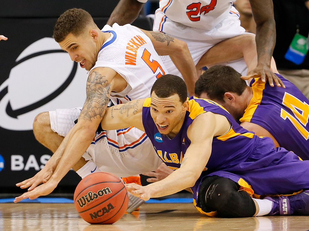 . ORLANDO, FL - MARCH 20:  Gary Johnson #20 of the Albany Great Danes and Scottie Wilbekin #5 of the Florida Gators go after a loose ball in the second half during the second round of the 2014 NCAA Men\'s Basketball Tournament at Amway Center on March 20, 2014 in Orlando, Florida.  (Photo by Kevin C. Cox/Getty Images)
