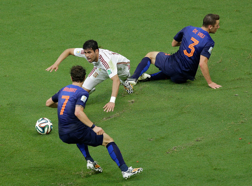 . Spain\'s Diego Costa falls after being tackled by Netherlands\' Stefan de Vrij next to Netherlands\' Daryl Janmaat (7) during the group B World Cup soccer match between Spain and the Netherlands at the Arena Ponte Nova in Salvador, Brazil, Friday, June 13, 2014.  (AP Photo/Christophe Ena)