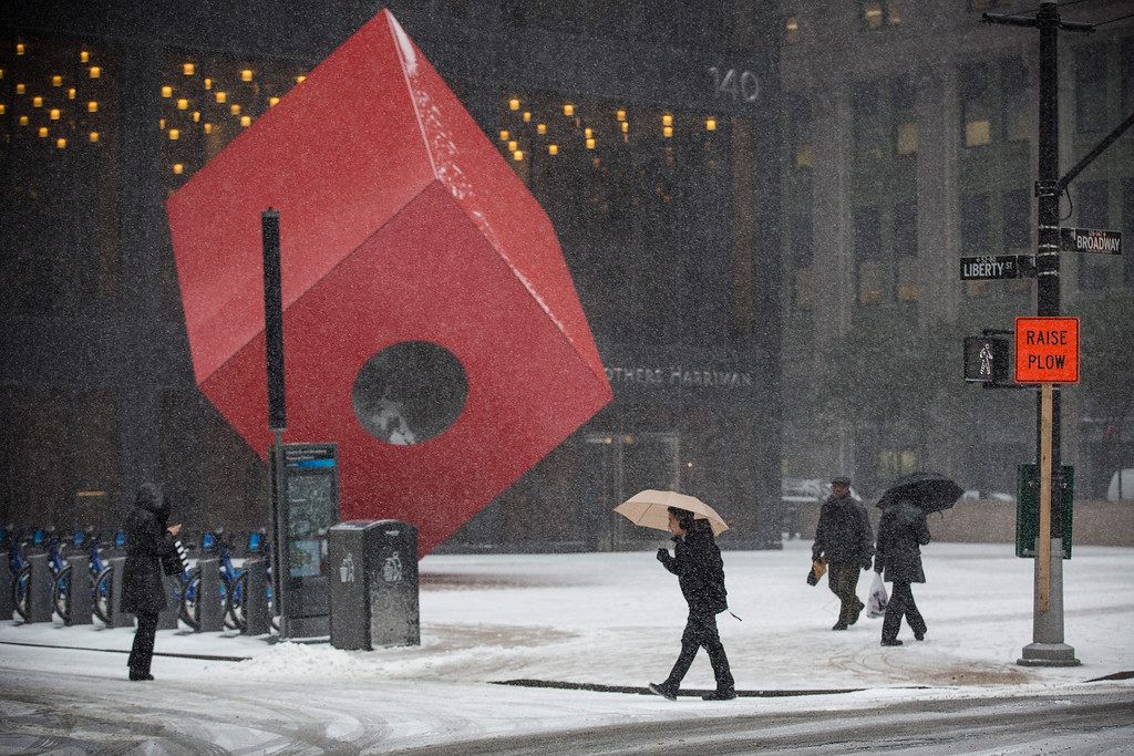 ". People walk past the art installation ""Red Cube\"" by Isamu Noguchi during a snow storm that is moving through the Northeast on January 21, 2014 in New York City. (Photo by Andrew Burton/Getty Images)"