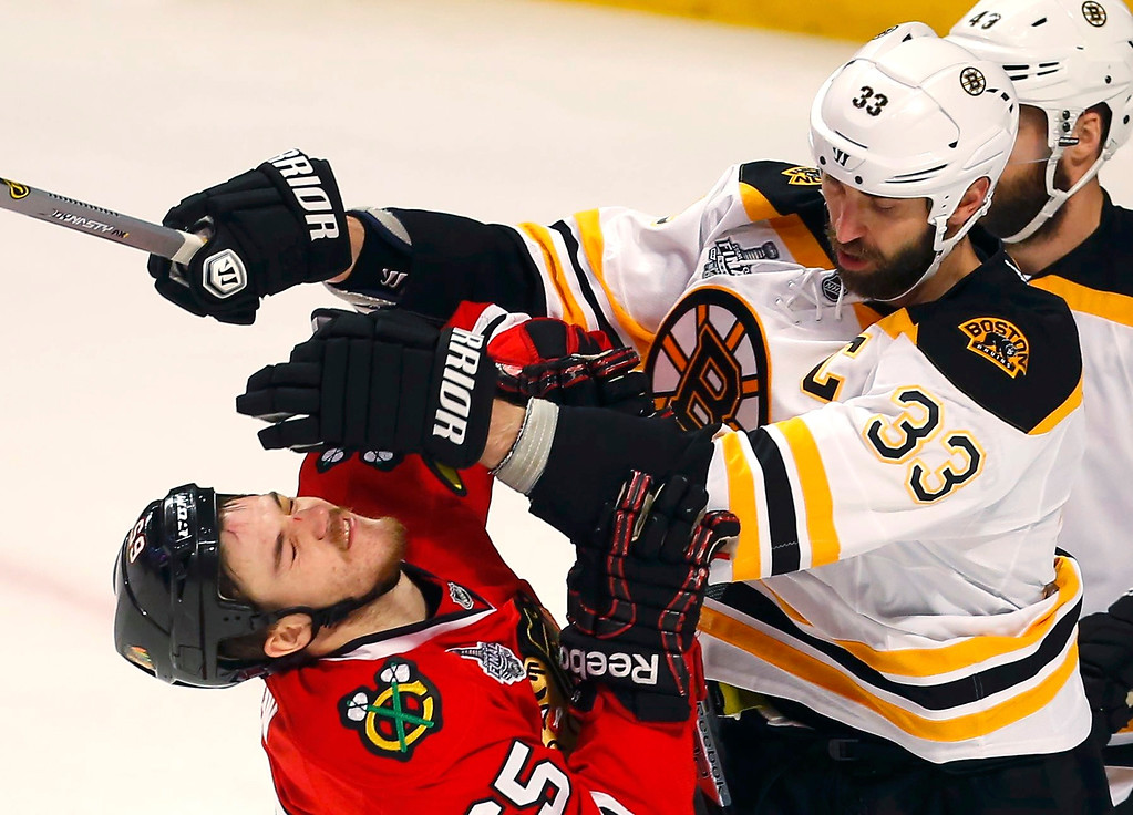 . Boston Bruins\' Zdeno Chara (33) shoves Chicago Blackhawks\' Andrew Shaw during the first period in Game 1 of their NHL Stanley Cup Finals hockey series in Chicago, Illinois, June 12, 2013. REUTERS/Jeff Haynes