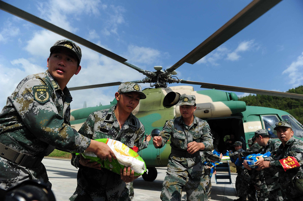 . YA\'AN, CHINA - APRIL 24:  (CHINA OUT) Rescuers load relief supplies onto a helicopter on April 24, 2013 in Ya\'an, China. A powerful earthquake struck the steep hills of China\'s southwestern Sichuan province on the morning of April 20, leaving at least 196 people dead and more than 12,200 injured.  (Photo by ChinaFotoPress/ChinaFotoPress via Getty Images)