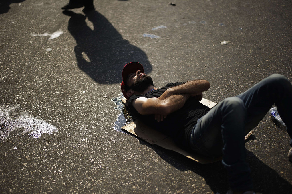 . A protestor rests on the ground as members of the Muslim Brotherhood and supporters of Egypt\'s ousted president Mohammed Morsi demonstrate outside the High Court in Cairo on August 12, 2013. Egypt\'s judiciary said it was extending Morsi\'s detention for a further 15 days pending an investigation into his collaboration with Hamas, which rules neighboring Gaza.   GIANLUIGI GUERCIA/AFP/Getty Images