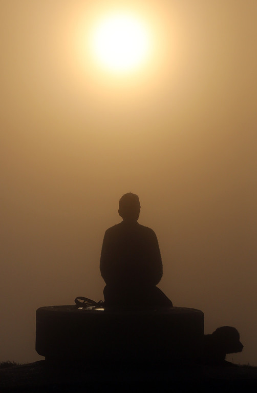 . A dog walker takes in the view at the top of Glastonbury Tor as the rising sun begins to clear the early morning mist and fog near the town of Glastonbury on September 4, 2013 in Somerset, England.  (Photo by Matt Cardy/Getty Images)