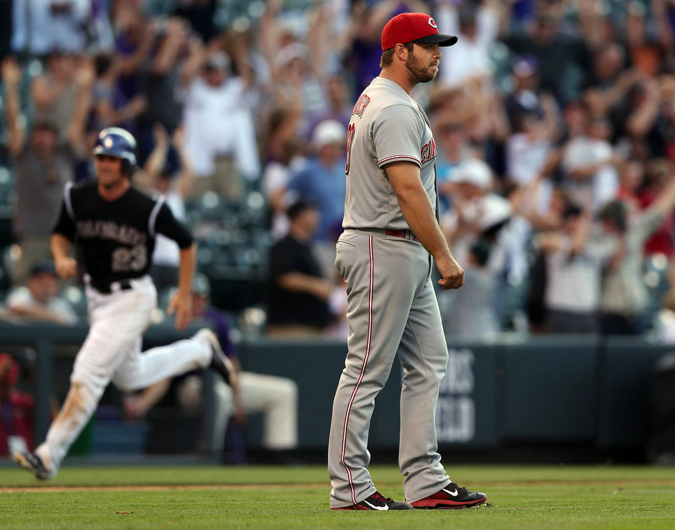 . Cincinnati Reds relief pitcher J.J. Hoover, front, reacts after giving up a three-run walkoff home run to Colorado Rockies\' Drew Stubbs in the ninth inning of the Rockies\' 10-9 victory in a baseball game in Denver, Sunday, Aug. 17, 2014. (AP Photo/David Zalubowski)
