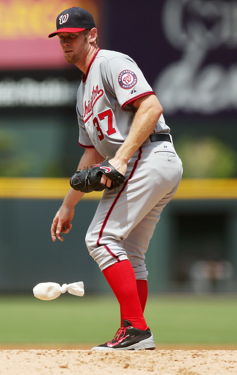 . Washington Nationals starting pitcher Stephen Strasburg reacts after giving up an RBI-single to Colorado Rockies\' Michael McKenry in the first inning of a baseball game in Denver on Wednesday, July 23, 2014. (AP Photo)