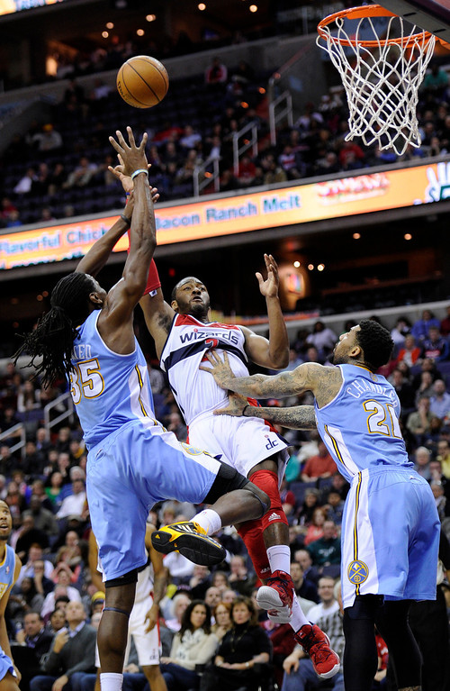 . Washington Wizards guard John Wall, center, takes a shot against Denver Nuggets\' Kenneth Faried (35) and Wilson Chandler (21) during the second half of an NBA basketball game, Friday, Feb. 22, 2013, in Washington. The Wizards won 119-113. (AP Photo/Nick Wass)