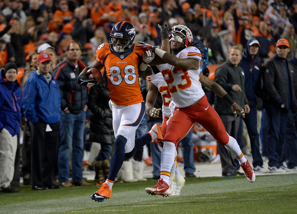 . Denver Broncos wide receiver Demaryius Thomas (88) tries to ward off and tackle by Kansas City Chiefs free safety Kendrick Lewis (23) as he is pushed out of bounds in the second quarter. The Denver Broncos take on the Kansas City Chiefs at Sports Authority Field at Mile High in Denver on November 17, 2013. (Photo by Joe Amon/The Denver Post)