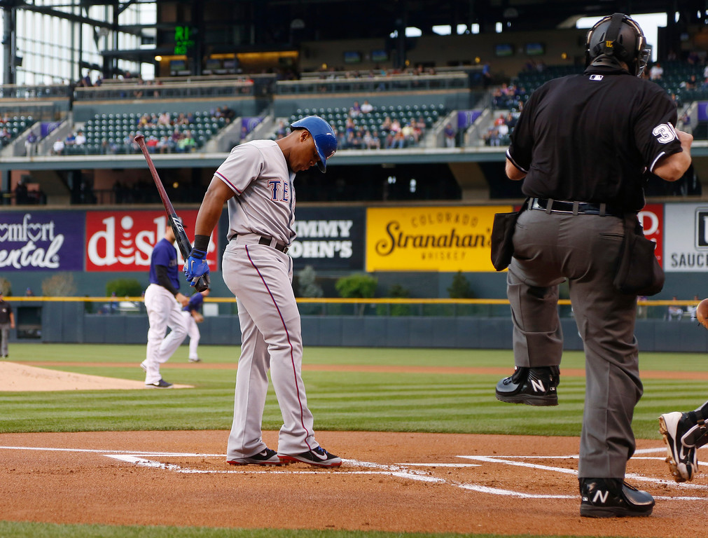 . Texas Rangers\' Adrian Beltre, left, reacts to called strike three by home plate umpire Gary Cedarstrom to end the top of the first inning against the Colorado Rockies in an interleague baseball game in Denver on Monday, May 5, 2014. (AP Photo/David Zalubowski)
