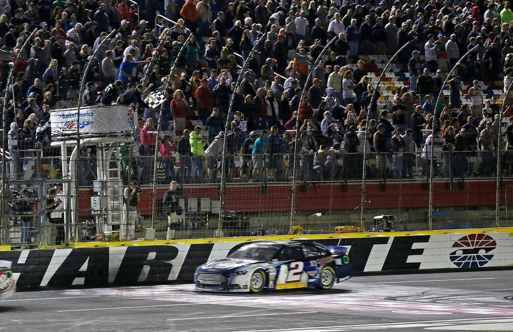 . Brad Keselowski (2) takes the checkered flag to win the NASCAR Sprint Cup Series auto race at Charlotte Motor Speedway in Concord, N.C., Saturday, Oct. 12, 2013. (AP Photo/Gerry Broome)