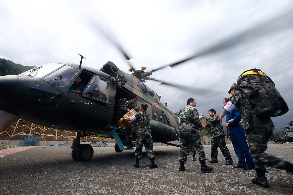 . Rescue workers load relief supplies onto a helicopter to be transported to the earthquake-hit area of Lushan county, at Chengdu airport, Sichuan province April 20, 2013. A strong 6.6 magnitude earthquake hit the remote, mostly rural and mountainous area of Lushan county in southwestern China\'s Sichuan province on Saturday, killing at least 156 people and injuring about 5,500 close to where a big quake killed almost 70,000 people in 2008. REUTERS/Stringer