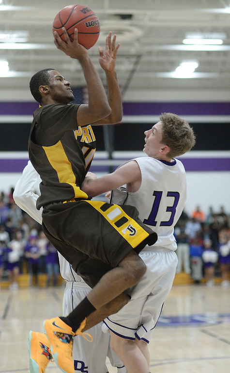 . Spartans\' senior guard Domenik Brewer (11) went to the basket against Rebels\' defender Turner Dumas Peterson (13) in the third quarter. Photo By Karl Gehring/The Denver Post