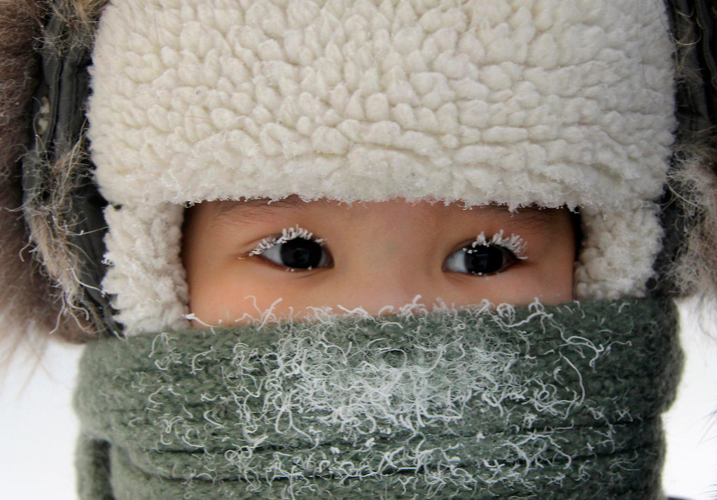 . A child, with eyelashes covered with hoarfrost, is seen along a street in the eastern Siberian city of Yakutsk in Sakha (Yakutia) Republic February 10, 2012. The air temperature in Yakutsk is about minus 35 degrees Celsius (minus 31 degrees Fahrenheit).  REUTERS/Viktor Everstov