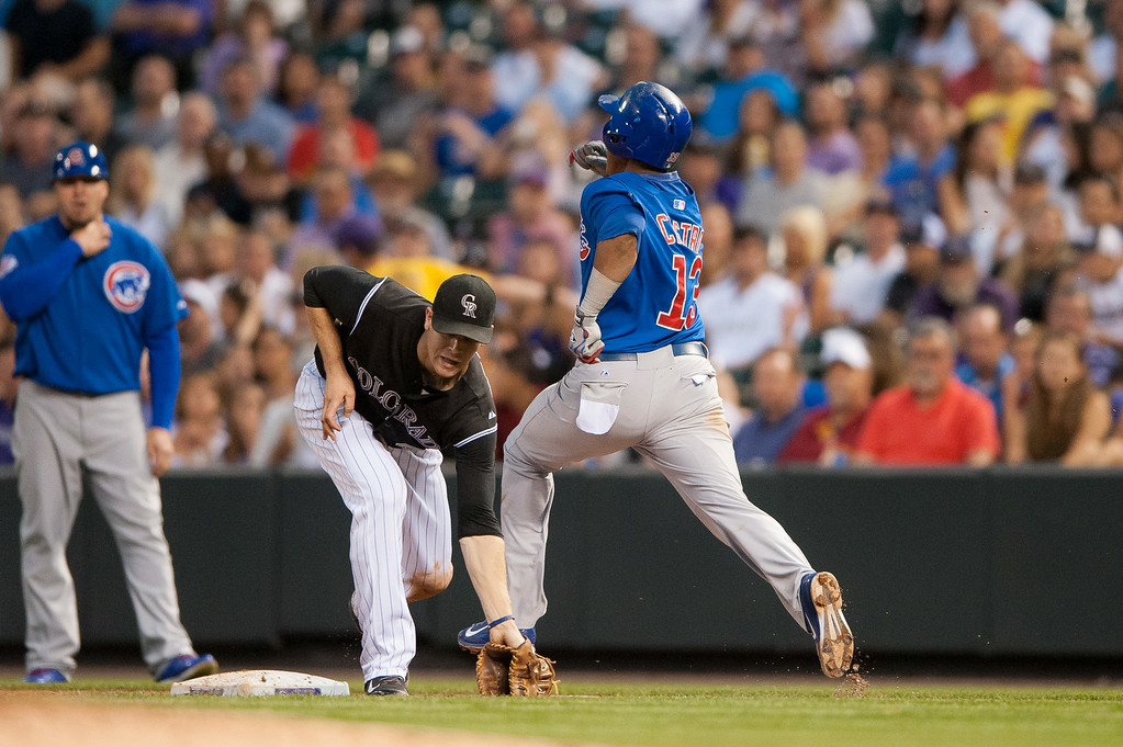 . DENVER, CO - AUGUST 06:  Starlin Castro #13 of the Chicago Cubs reaches first base with a single as the throw pulls Justin Morneau #33 of the Colorado Rockies off the bag in the sixth inning of a game at Coors Field on August 6, 2014 in Denver, Colorado.  (Photo by Dustin Bradford/Getty Images)