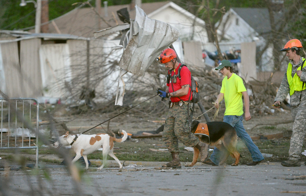 . A K-9 rescue unit walks along Military Street in Baxter Springs, Kan., April 27, 2014, as they survey the damage from Sunday\'s tornado.  A powerful storm system rumbled through the central and southern United States on Sunday, spawning a massive tornado that  carved through Little Rock\'s northern suburbs and another that hit Oklahoma and Kansas. (AP Photo/The Joplin Globe, Roger Nomer )