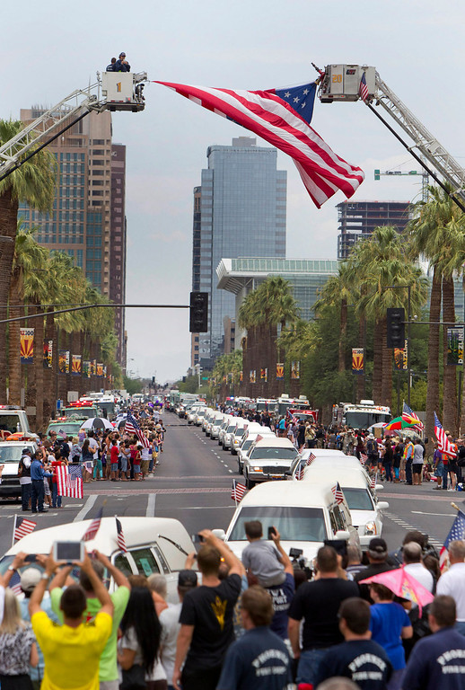 . A procession of 19 hearses for the 19 firefighters killed in a wildfire a week ago drives through Phoenix, Sunday, July 7, 2013 The elite crew of firefighters were overtaken by the out-of-control blaze as they tried to protect themselves from the flames under fire-resistant shields. (AP Photo/The Arizona Republic, Cheryl Evans)