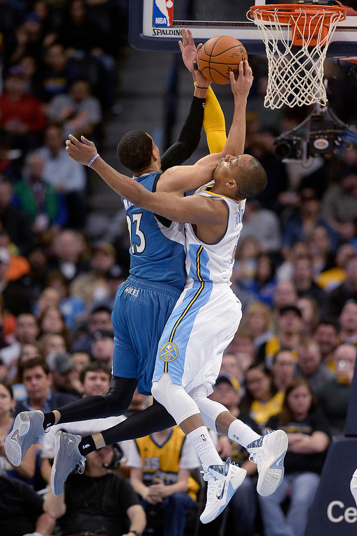 . Randy Foye (4) of the Denver Nuggets fouls Kevin Martin (23) of the Minnesota Timberwolves during the second quarter at the Pepsi Center.  (Photo By AAron Ontiveroz/The Denver Post)