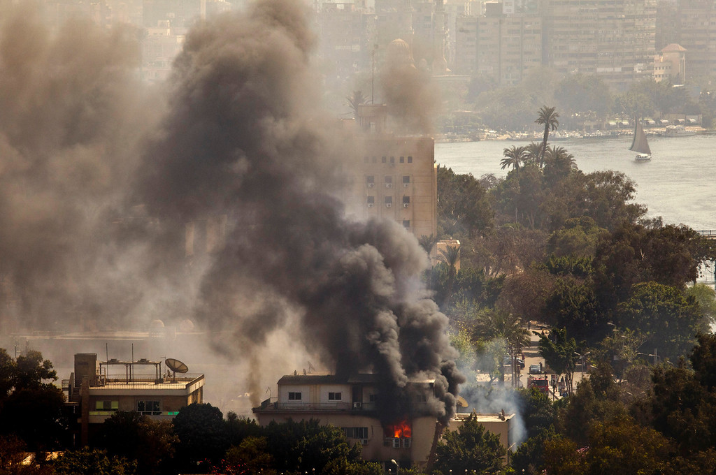. Smoke and fire rises from the Egyptian Soccer Federation after protesters set fire following a court verdict in, Cairo, Egypt, Saturday, March 9, 2013. (AP Photo/Maya Alleruzzo)