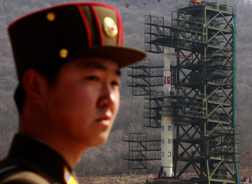 . A soldier stands guard in front of the Unha-3 (Milky Way 3) rocket sitting on a launch pad at the West Sea Satellite Launch Site, during a guided media tour by North Korean authorities in the northwest of Pyongyang April 8, 2012.   REUTERS/Bobby Yip