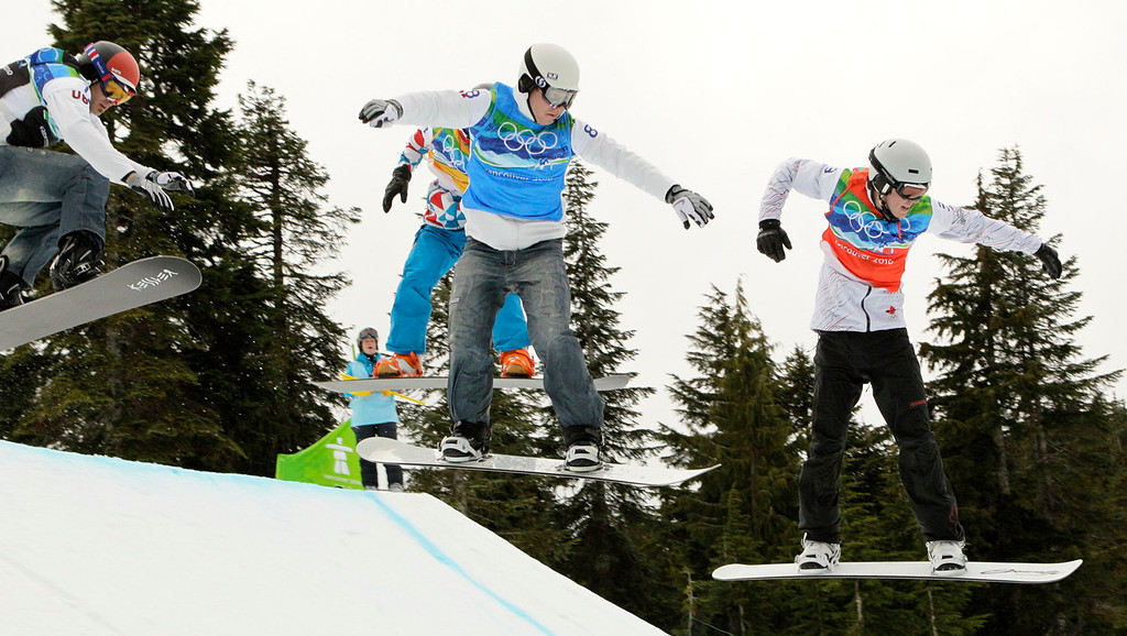 . Mike Robertson of Canada, right, leads, Nate Holland of the USA, center and Seth Wescott of the USA, left during the snowboard cross final at the Vancouver 2010 Olympics in Vancouver, British Columbia, Monday, Feb. 15, 2010. (AP Photo/Jae C. Hong)