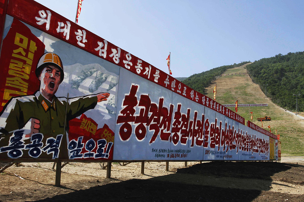 """. North Korean propaganda stands at the base of a ski slope at a ski resort building project at North Korea\'s Masik Pass on Aug. 23, 2013. The sign reads, from left to right, \""""Full attack. March Forward. Let\'s Absolutely Finish Building Masik Pass Ski Resort Within This Year By Launching A Full Aggressive War and Full Battle.\""""  (AP Photo/Kim Kwang Hyon)"""