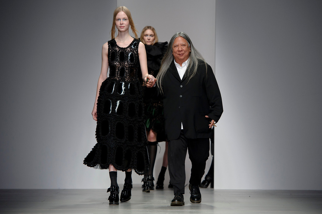 . Hong Kong born designer John Rocha, right, walks the runway,  during his London Fashion Week Autumn/Winter 2014 show, at Somerset House in central London, Saturday, Feb. 15, 2014. (Photo by Jonathan Short/Invision/AP)